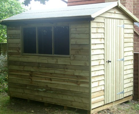 Small gable weatherboard shed with single door and fixed triple window