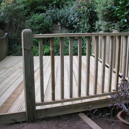 A decking area installed using grooved and reeded treated decking boards including a Tate Fencing hand rail
