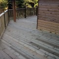 A full deck around a building installed by Tate Fencing for a customer, using grooved and reeded deck boards