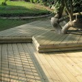 an double layered deck round a tree using grooved and reeded decking and machine half rails to finish off the edges