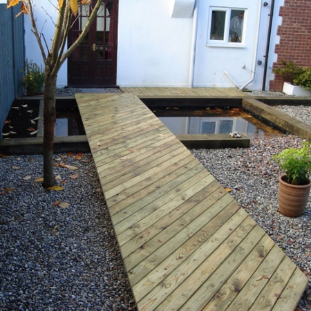 32 x 100mm bevelled decking used to create a contemporary walk way over a pond.