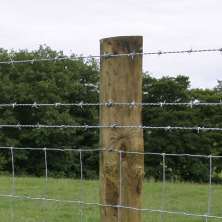 3 strands of barb wire installed on top of stock fencing