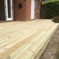A patio area with a small decking step made from our grooved and reeded softwood decking