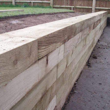 A softwood sleeper wall installed as a retaining wall to hold back soil.