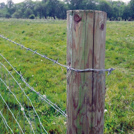 The barbed wire attached tight to the post.