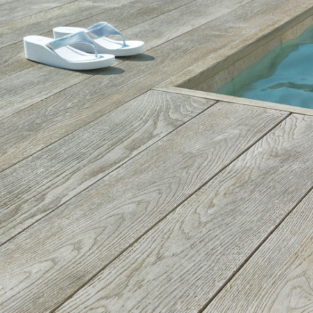 Enhanced grain composite decking a round a swimming pool.