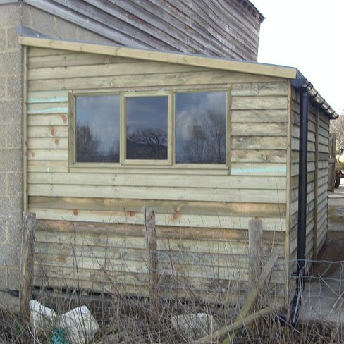 Triple window detail in end of pent weatherboard shed example