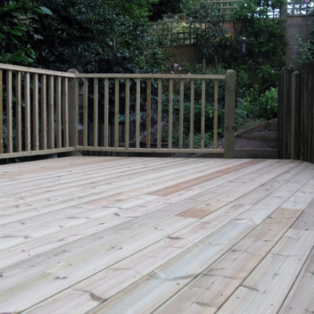 A decking with hand rail installed using grooved and reeded treated decking boards