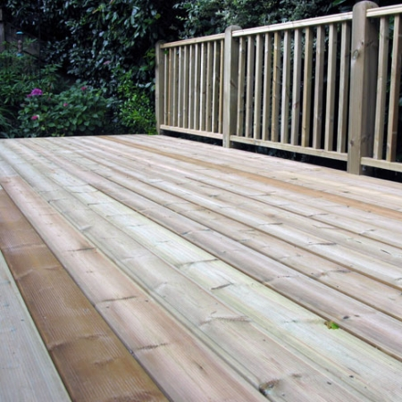 A decking area including a Tate Fencing hand rail installed using grooved and reeded treated decking boards