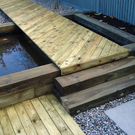 Our bevelled decking used to create a contemporary walk way over a pond.