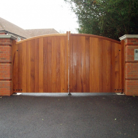 An automated pair of Iroko hardwood sherborne gates